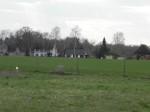 im Vordergrund Brachfläche der Schlammgrube und deren Setzungspegeln, im Hintergrund nächst gelegene Wohnhäuser von Luckau in 300 m Entfernung