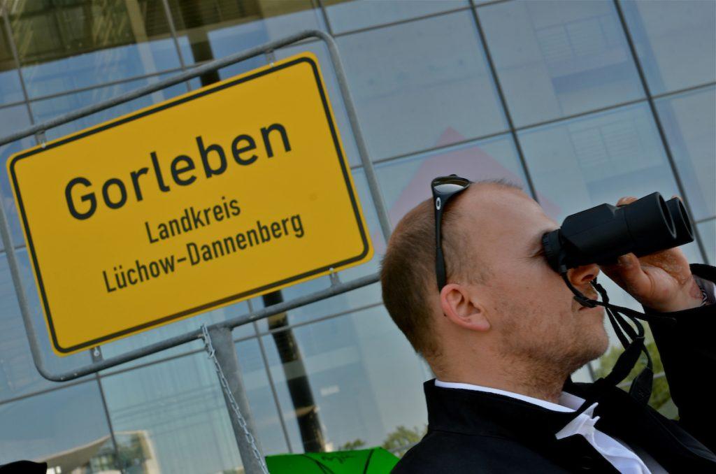 """Am 22. Mai 2014 nahm die Endlagerkommission die Arbeit auf. Dagegen hat die Bürgerinitiative Lüchow-Dannenberg in Berlin und in Gorleben protestiert. Die Kommission als Teil des Standortauswahlgesetzes suggeriere, dass die Endlagersuche neu gestartet werde. Statt wirklich einen Schlussstrich unter die Tricks, Lügen und Verdrehungen der letzen drei Jahrzehnte zu ziehen, bleibe Gorleben als Standort gesetzt, so die BI. Durch das Gesetz und das Beteiligungsverfahren - die Endlagersuchkommission - sollen Umweltverbände eingebunden werden, um Gorleben im Nachhinein zu legitimieren. """"Welch Zeitverschwendung"""", so die BI, """"dass nun zwei Jahre lang offen und versteckt über einen Standort gestritten wird, statt eine umfassende Atommülldebatte einzuleiten!"""" Im Bild: Torben Klages, hauptamtlicher Mitarbeiter der Bürgerinitiative Lüchow-Dannenberg  Ort: Berlin Copyright: Kina Becker Quelle: PubliXviewinG"""