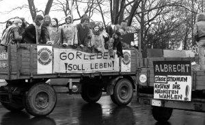 Der Abschluss des Gorleben-Trecks wird zur bis dahin größten Demonstration der Anti-AKW-Bewegung in der Bundesrepublik. Rund 100.000 Menschen empfangen den Treck der Bauern am 31. März 1979 in Hannover. Als Mahnmal und Erinnerung an den Treck bringen die Bauern einen großen Findling (»Gorleben-Stein«) mit, der bis heute am Weißekreuzplatz zu besichtigen ist. -- Die große Zahl der Teilnehmer ist auch auf einen Vorfall zurückzuführen, der sich wenige Tage zuvor in den USA ereignete. Im Atomkraftwerk Harrisburg (USA) kommt es am 28. März 1979 zu einem schweren Störfall, bei dem eine radioaktive Wolke aus der Anlage entweicht. Rund 200.000 Menschen müssen evakuiert werden. Ein noch schwererer Unfall konnte nur knapp vermieden werden. WAA, Anti AKW Bewegung, Treck der Bauern, Gorleben-Stein, Harriaburg, 19790331, 19790328, atomares Endlager, Gorleben-Treck, Gorleben